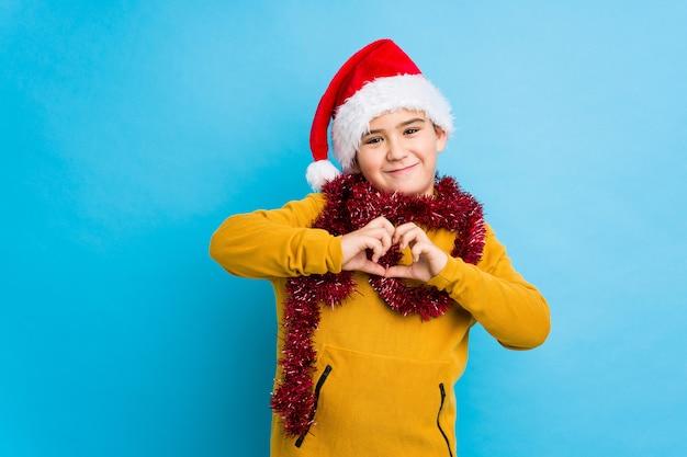 Petit garçon fête le jour de noël, coiffé d'un bonnet de noel isolé souriant et montrant une forme de coeur avec les mains.