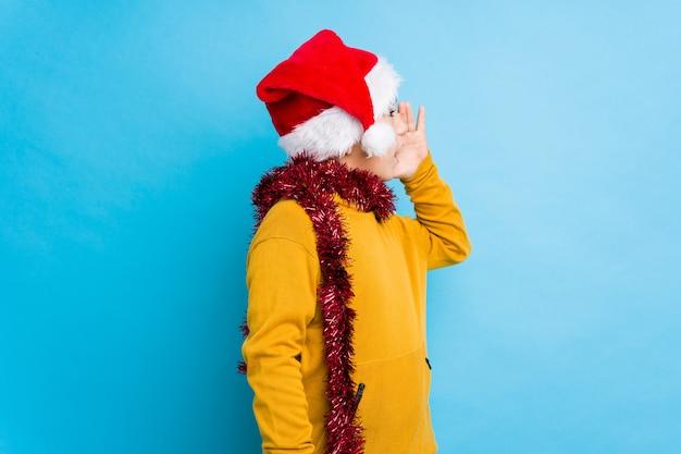 Petit garçon fête le jour de noël portant un bonnet de noel isolé criant et tenant palm près de la bouche ouverte.