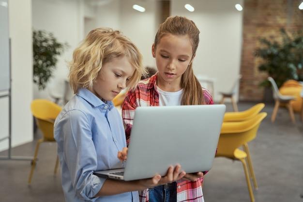 Petit garçon et fille apprenant la programmation en regardant l'écran d'un ordinateur portable en se tenant debout dans une salle de classe
