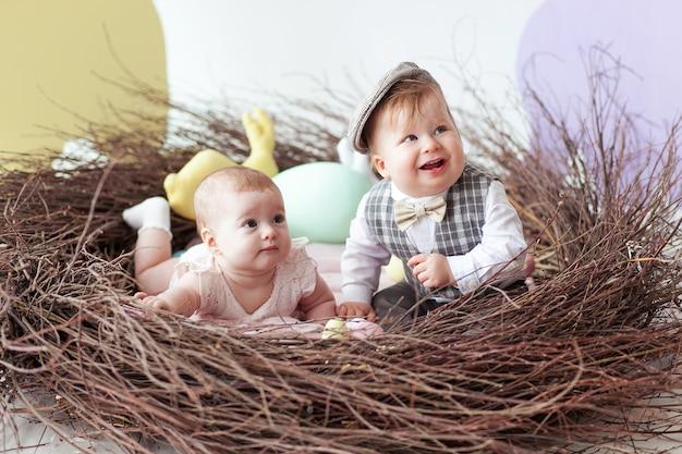 Petit garçon et une fille assis dans un nid naturel avec des oeufs de pâques colorés.