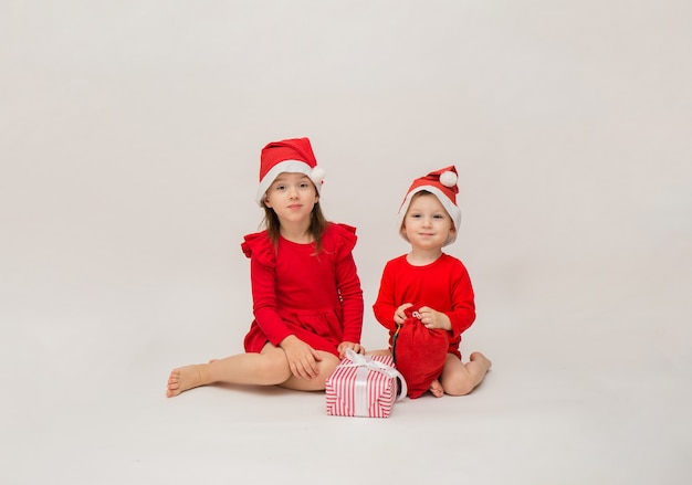Petit garçon et fille en chapeaux de noël avec des cadeaux assis sur blanc