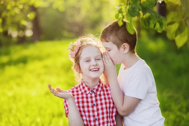 Petit garçon et fille chuchote.