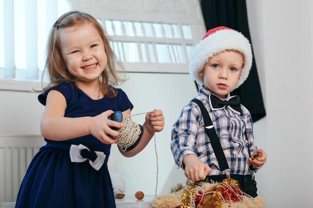 Petit garçon et fille dans les décorations de noël s'attendent à un miracle