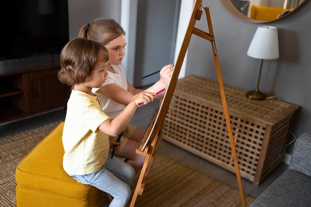 Petit garçon et fille dessinant ensemble à la maison à l'aide d'un chevalet
