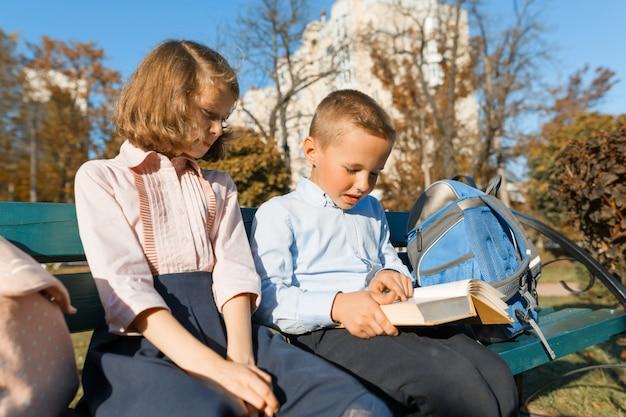 Petit garçon et fille écoliers lire un livre