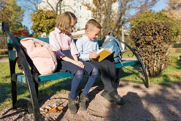 Petit garçon et fille écoliers lisant un livre