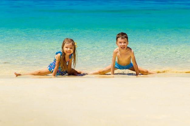 Petit garçon et fille faisant des divisions de gymnastique sur une plage tropicale de sable