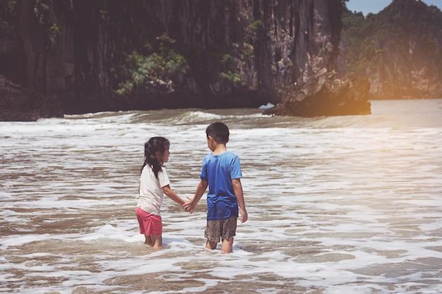 Petit garçon et fille jouant sur la plage