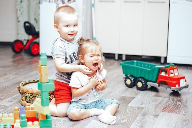 Petit garçon et fille jouent jouets fille bouleversée