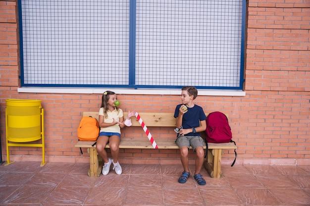 Petit garçon et fille mangeant une pomme à la récréation assis sur un banc en gardant une distance sociale.