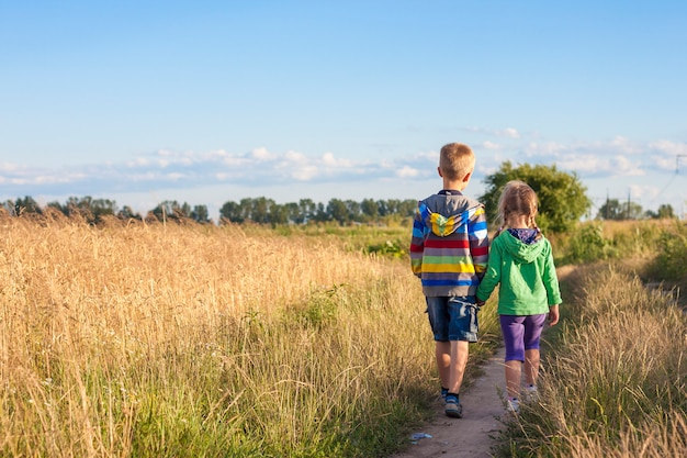 Petit garçon et fille, marcher ensemble, tenant mains
