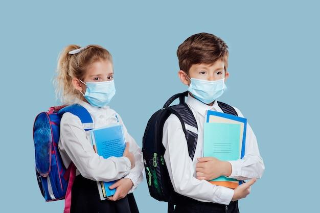 Petit garçon et fille avec masque médical et sac à dos a des cahiers et des livres à la main isolés sur bleu ...