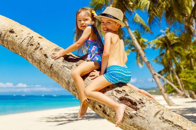 Petit garçon et fille s'amusant sur un cocotier sur une plage tropicale de sable. le concept de voyage et de vacances en famille.