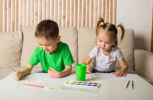 Petit garçon et une fille s'asseoir à une table et dessiner avec des peintures sur papier
