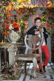 Petit garçon avec des fleurs dans le jardin en automne
