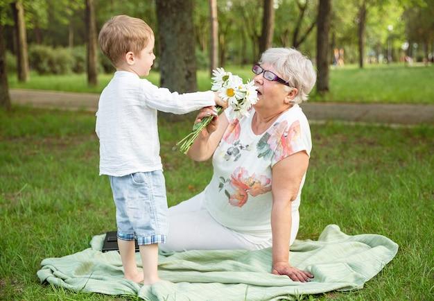 Petit garçon avec des fleurs et sa grand-mère dans le parc. bonne fête des mères
