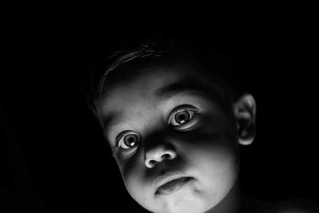 Petit garçon sur fond noir avec une lumière reflétant sur son visage