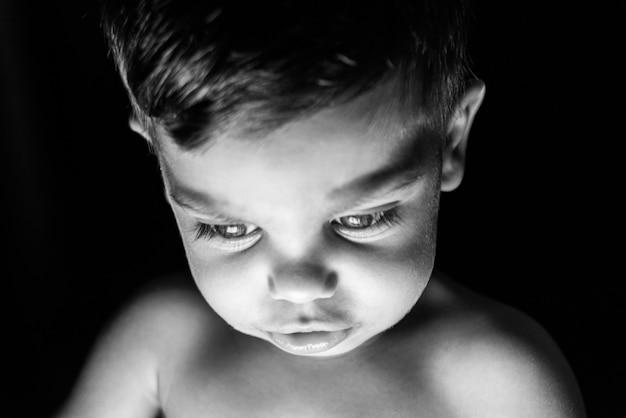 Petit garçon sur fond noir avec de la lumière se reflétant sur son visage