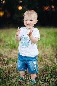 Petit garçon frappant des mains dans le parc.