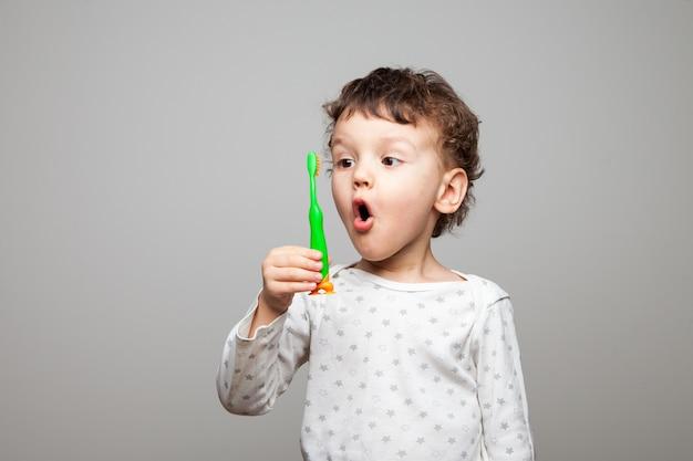 Un petit garçon, un gamin avec une brosse à dents à la main, regarde le comptoir, est surpris. regard enthousiaste. procédures hygiéniques. fond blanc isolé