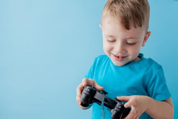 Petit garçon garçon 2-3 ans portant des vêtements bleus tenir en main joystick pour portrait en studio gameson fond bleu enfants. concept de mode de vie des gens enfance espace de copie maquette