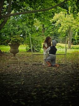 Petit garçon à genoux devant une petite fille dans un jardin entouré de verdure