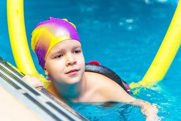 Un petit garçon avec un gilet de sauvetage sur la poitrine apprend à nager dans une piscine intérieure.
