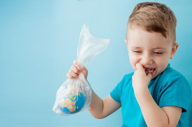 Petit garçon avec un globe dans un emballage sur fond bleu