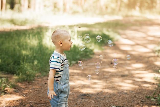 Petit garçon gonflant des bulles de savon en été dans la nature