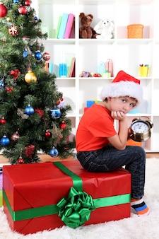 Petit garçon avec un gros cadeau et une horloge en prévision du nouvel an