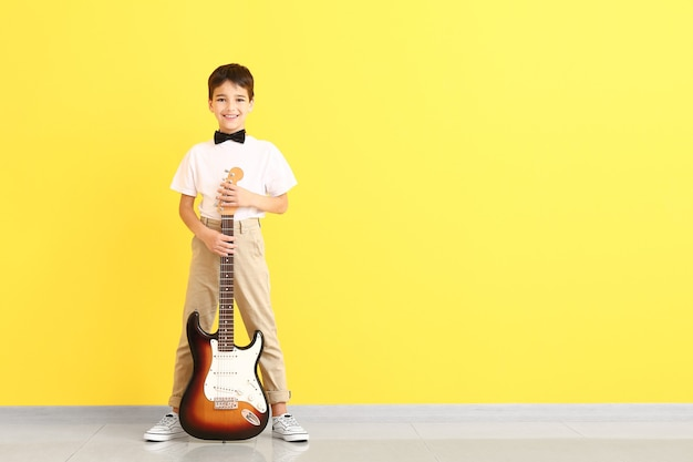 Petit garçon avec guitare près de la surface de couleur