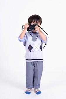 Petit garçon heureux avec caméra sur blanc