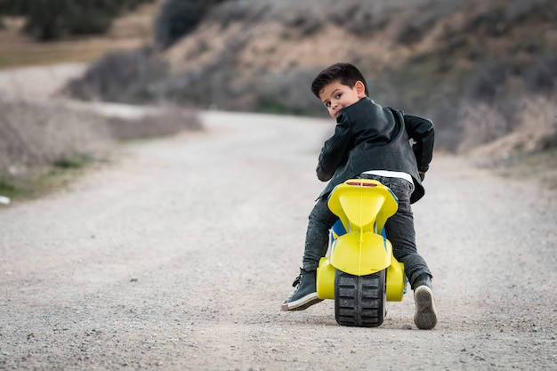 Un petit garçon heureux conduisant une moto de jouet, vêtu d'une veste de motard en cuir sur une route de campagne