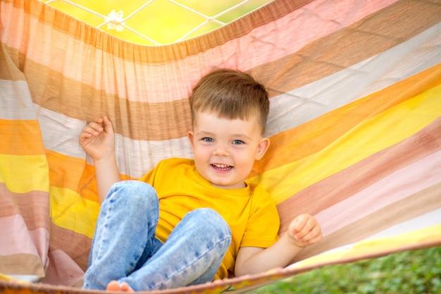 Petit garçon heureux d'équitation dans un hamac lumineux dans son parc. vacances d'été pour les enfants