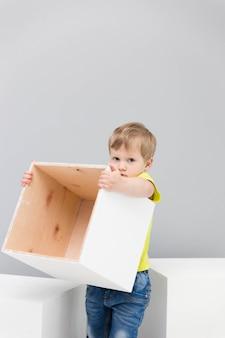 Petit garçon heureux jouant avec de gros cubes blancs