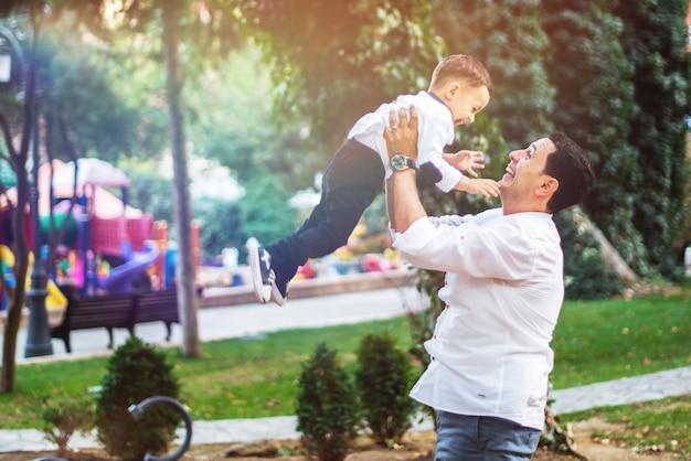 Petit garçon heureux avec son père dans le jardin. notion de famille heureuse.
