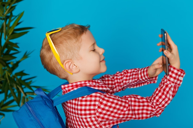 Petit garçon hipster avec sac à dos et lunettes de soleil tenant un téléphone