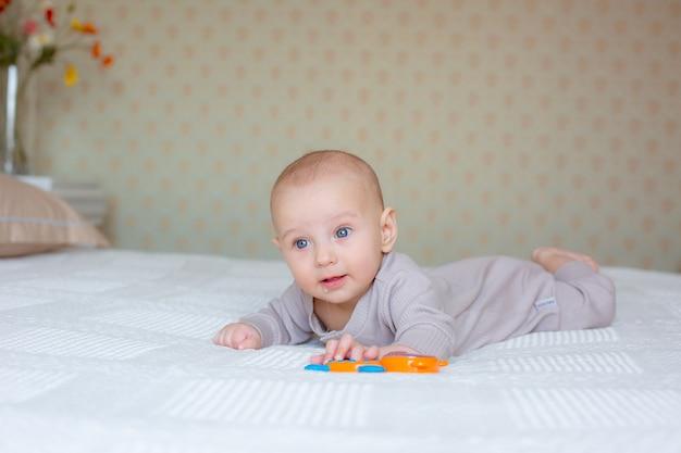Petit garçon avec un hochet sur le lit