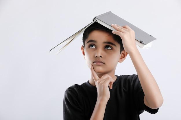 Petit garçon indien / asiatique avec livre sur la tête et penser sérieusement