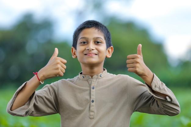 Petit garçon indien / asiatique montrant les pouces vers le haut
