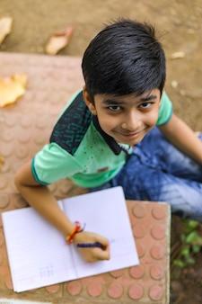 Petit garçon indien écrit sur carnet de notes