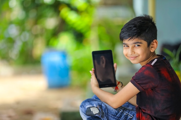 Petit garçon indien montrant l'écran du smartphone