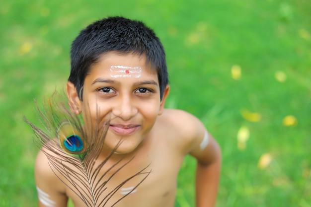 Petit garçon indien se faisant passer pour le seigneur krishna