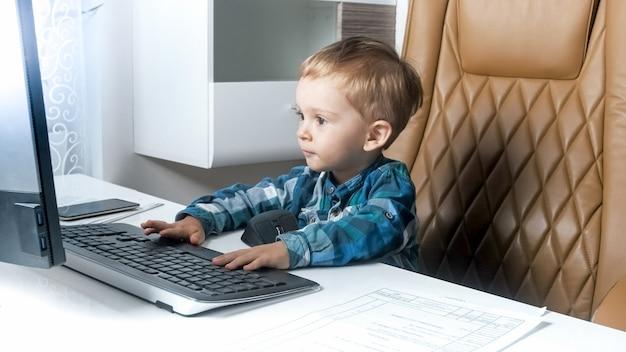 Petit garçon intelligent en bas âge assis au bureau et travaillant sur ordinateur.