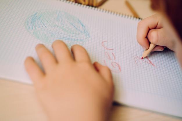 Petit garçon intelligent dessinant la planète terre et apprenant les problèmes environnementaux.