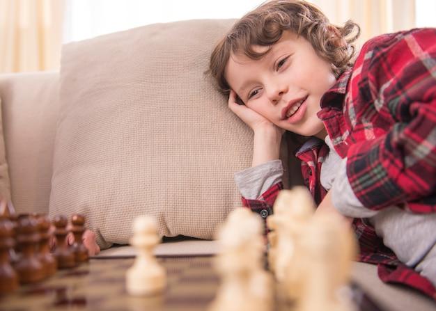 Petit garçon intelligent sourit en jouant aux échecs.