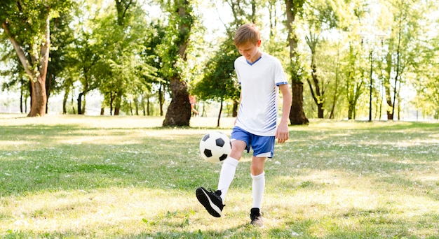 Petit garçon jouant au football seul