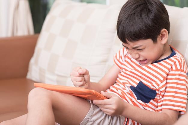 Petit garçon jouant au jeu sur tablette