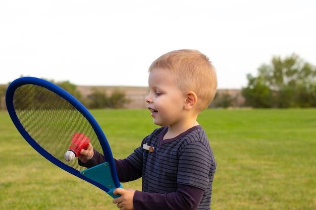 Petit garçon jouant au tennis au parc