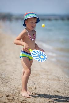 Petit garçon jouant aux pagaies sur la plage